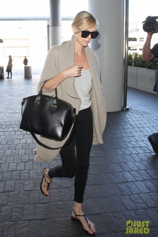 Charlize Theron keeps her head low as arrives at LAX to catch her flight